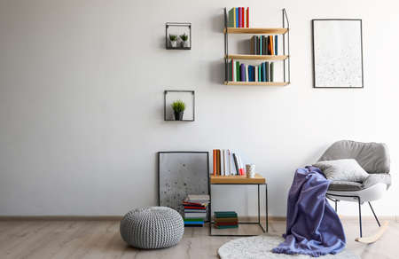 Comfortable armchair and different books near wall in room, space for text