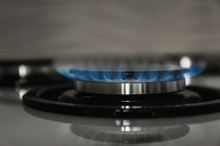 Gas burner with blue flame on modern stove, closeup