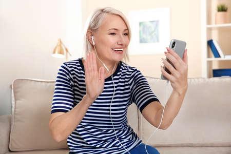 Donna matura che utilizza la chat video sul telefono cellulare a casa Archivio Fotografico