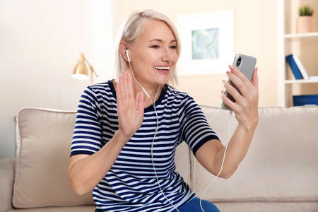 Rijpe vrouw die thuis videochat op mobiele telefoon gebruikt Stockfoto