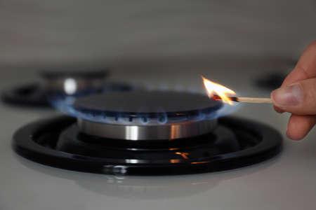 Femme allumant une cuisinière à gaz avec une allumette, gros plan