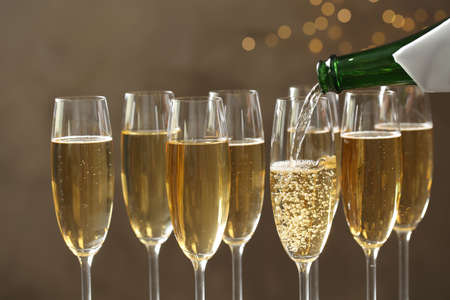 Pouring champagne into glasses on blurred background, closeup 免版税图像