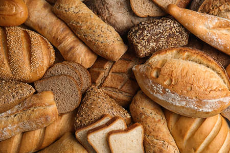 Différentes sortes de pain frais en arrière-plan, vue de dessus Banque d'images