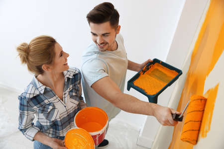 Happy couple painting wall indoors, above view. Home repair Imagens