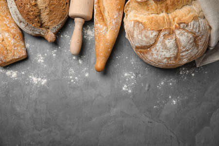 Different kinds of fresh bread on grey table, flat lay. Space for text