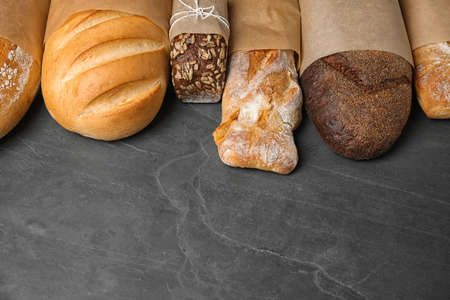 Different kinds of fresh bread on grey table, space for text 스톡 콘텐츠
