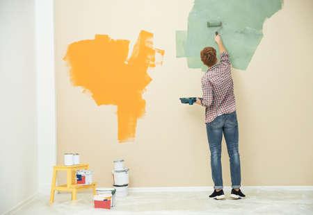 Junger Mann Malerei Wand drinnen, Platz für Text. Reparatur zu Hause