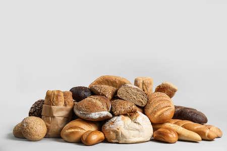 Pile of fresh tasty bread on light background Banco de Imagens