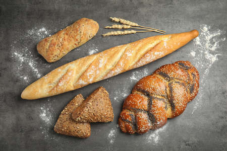 Different kinds of fresh bread on grey table, flat lay