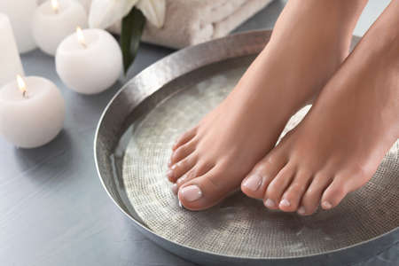 Close-upmening van vrouw die haar voeten in schotel met water op grijze vloer onderdompelen. Spa behandeling