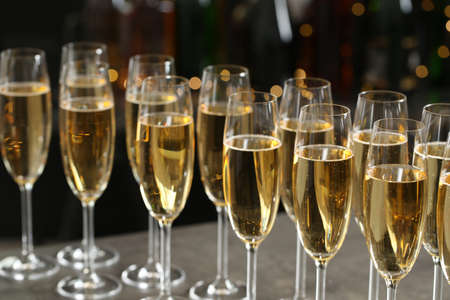 Many glasses of champagne on blurred background, closeup