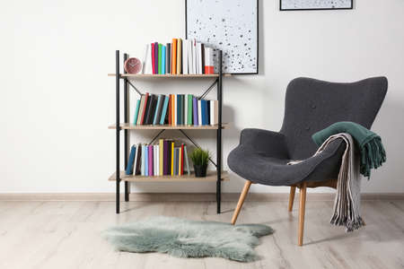 Comfortable armchair and shelving unit with different books near wall in room Stock fotó