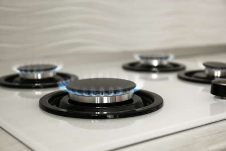 Gas burners with blue flame on modern stove, closeup. Space for text