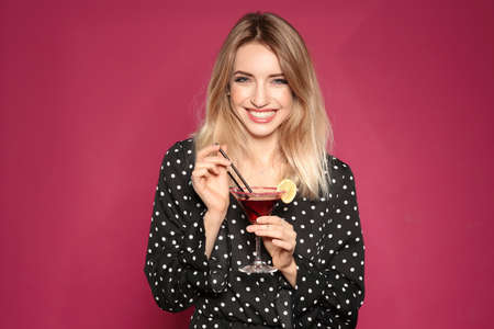 Beautiful young woman with glass of martini cocktail on color background 版權商用圖片