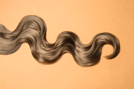Lock of brown wavy hair on color background, top view Standard-Bild