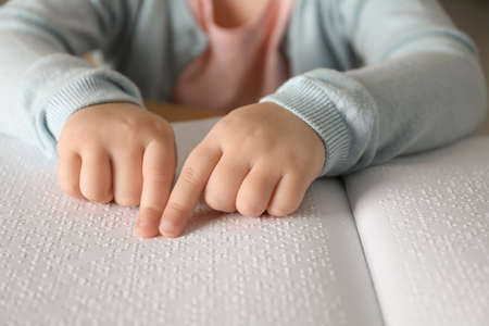 Blind child reading book written in Braille, closeup