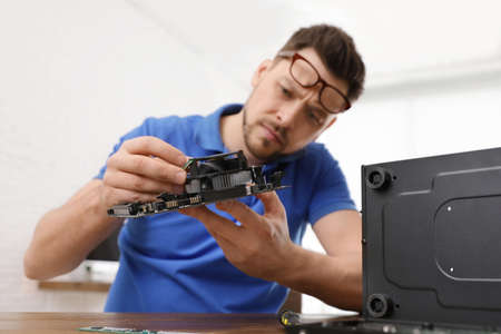 Male technician repairing computer at table indoors