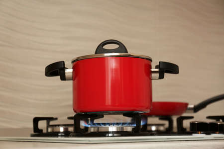 Red pot and frying pan on modern gas stove Imagens