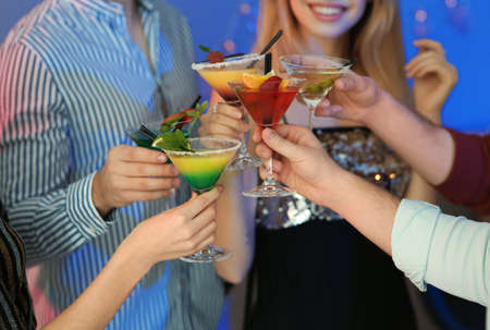 Group of young people holding martini cocktails at party, closeup