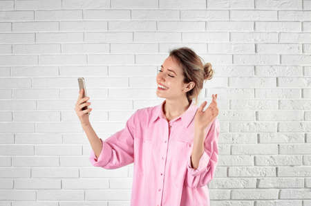 Woman using mobile phone for video chat against brick wall Stockfoto - 123098091