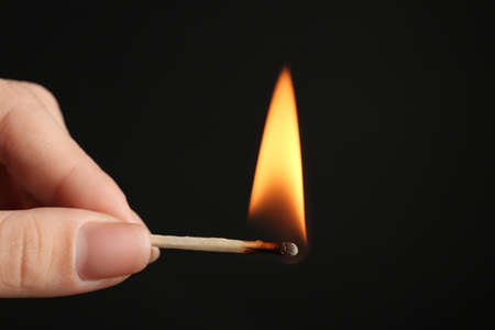 Woman holding burning match on black background, closeup. Space for text Stock Photo