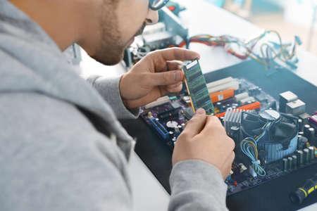 Male technician repairing motherboard at table, closeup