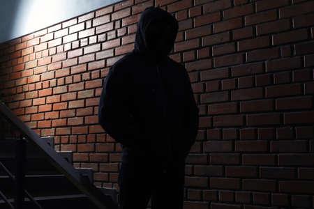 Silhouette of mysterious man in hoodie indoors. Dangerous criminal Reklamní fotografie