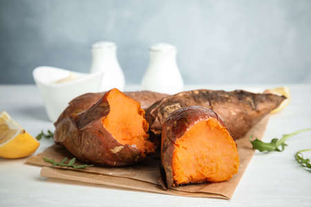 Delicious baked sweet potatoes on white table
