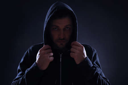 Mysterious man in hoodie on dark background. Dangerous criminal Reklamní fotografie