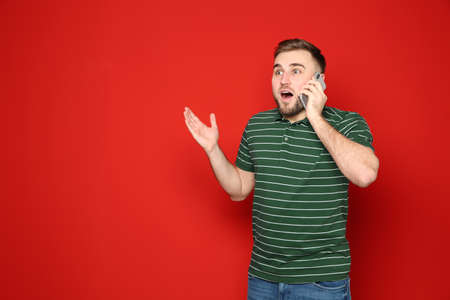 Portrait of emotional man talking on phone against color background. Space for text