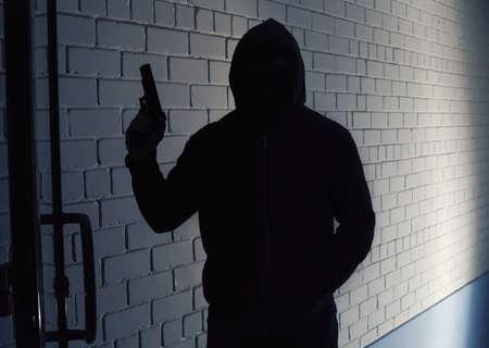 Silhouette of man with gun in hoodie indoors. Dangerous criminal Stock fotó