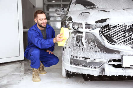 Worker cleaning automobile with sponge at professional car wash