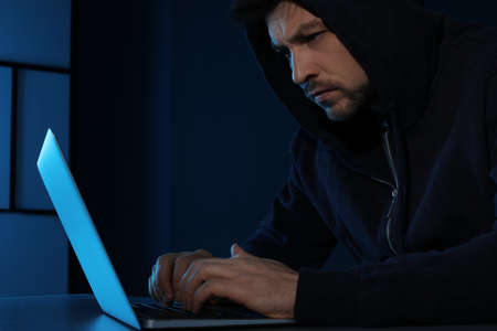 Man using laptop in dark room. Criminal offence