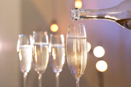 Champagne pouring from bottle into glass on blurred background, closeup. Space for text Stock fotó