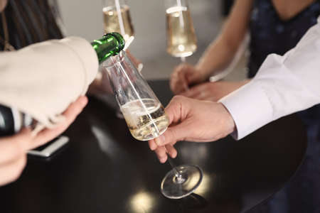 Waiter pouring champagne into man's glass at party, closeup Imagens - 123113037