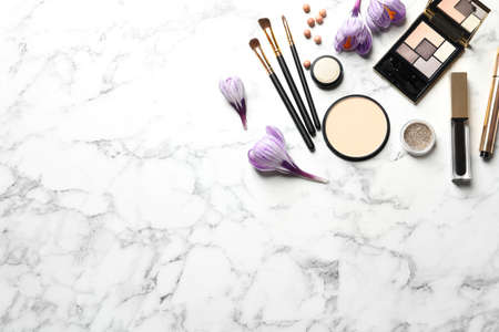Many different makeup products and spring flowers on marble background, flat lay. Space for text Imagens