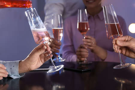 Woman filling glass with champagne and her friends at table in bar, closeup Stock Photo