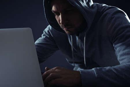 Man using laptop on dark background. Criminal activity Stockfoto