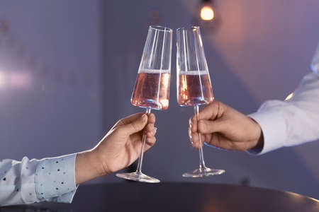 Man and woman with glasses of champagne on color background, closeup