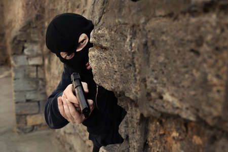 Masked man with gun hiding behind stone wall outdoors. Criminal offence Stockfoto - 123113153