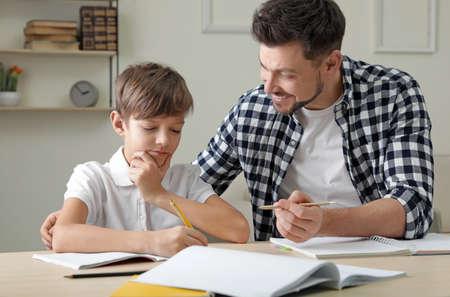 Papa helpt zijn zoon thuis met schoolopdracht Stockfoto