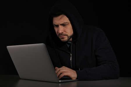 Man using laptop in darkness. Criminal activity