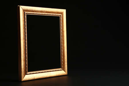 Empty golden frame on black background. Space for design