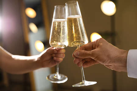 Man and woman clinking glasses of champagne on blurred background, closeup Stock fotó