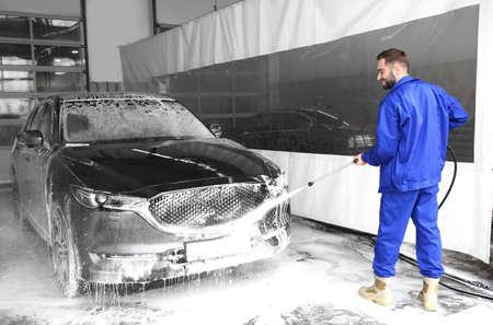 Arbeiter, der Automobil mit Hochdruckwasserstrahl an der Autowäsche reinigt Standard-Bild