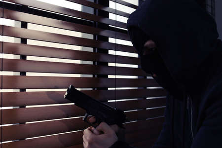 Masked man with gun spying through window blinds indoors. Dangerous criminal