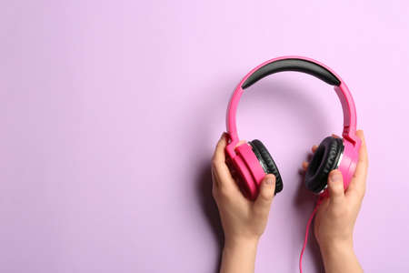 Woman holding stylish headphones on color background, closeup. Space for text