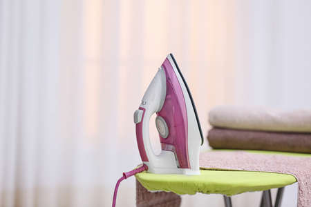 Modern iron and towels on board against blurred background. Space for text