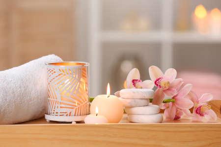 Komposition mit Kerzen, Blumen und Steinen auf Holztisch im Spa-Salon. Platz für Text
