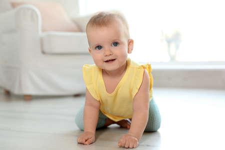 Cute baby girl on floor in room